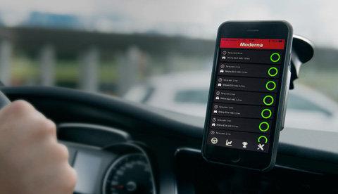 Kvinna styr bil och kollar samtidigt på sin telefon. Bilden representerar vår Smart bil försäkring.